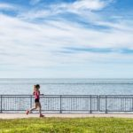 Woman in pink jogging on a trail next to the ocean