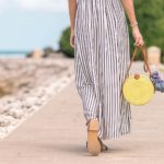 Woman walking to beach holding yellow purse